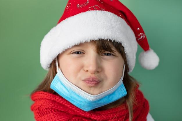 コロナウイルスの新年。サンタの帽子と緑の壁の保護医療マスクのかわいい女の子のクローズアップの肖像画。女の子はしかめっ面をし、変な顔をします。