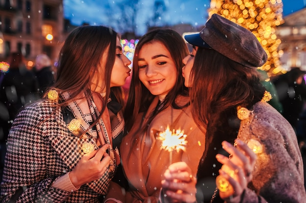 New year. women friends burning sparklers in lviv by christmas tree on street fair kissing on cheek having fun. happy girls celebrating under snow. party