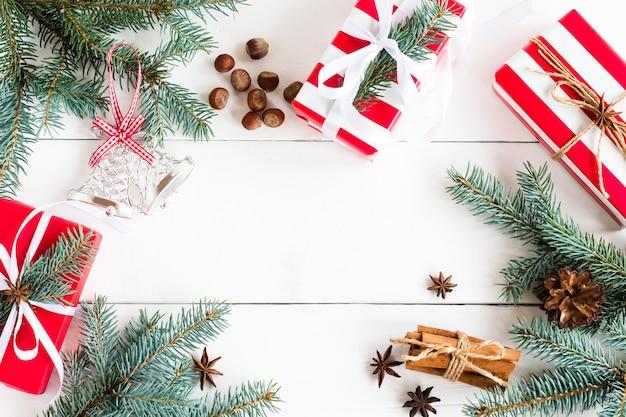 Новогодний деревянный фон с еловыми ветками, звездами аниса, палочками корицы, подарками в праздничной упаковке с копией пространства.