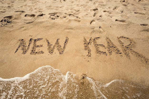 New year written on sandy beach and being washed by waves