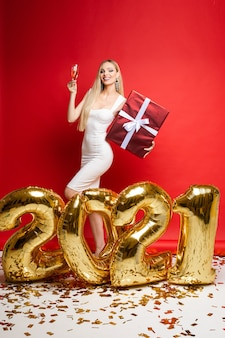 New year xmas celebrating, smiling girl with champagne, gift, golden balloons in 2021 shape, confetti on red wall.