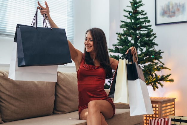 New year. young happy woman with shopping bags at home