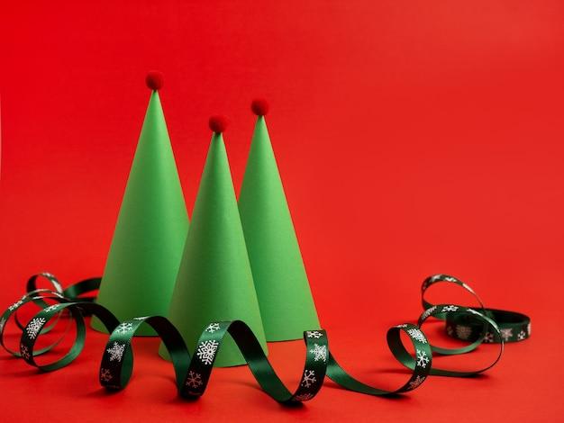 真っ赤な背景に紙の蛇紋岩で作られた新年カードクリスマスツリークリスマス装身具