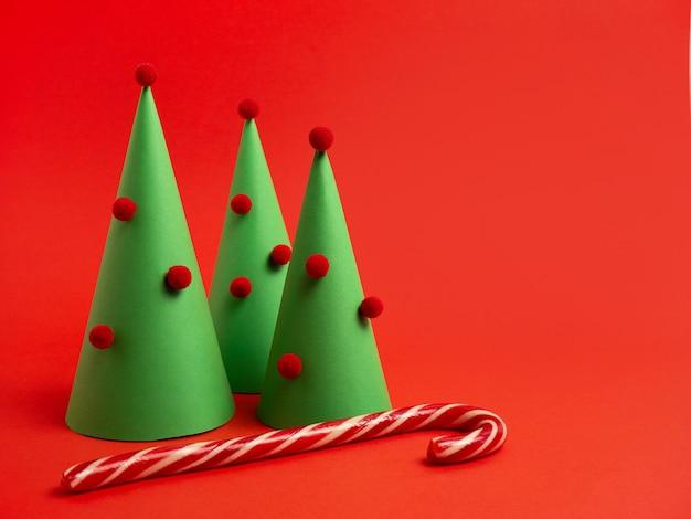 年賀状真っ赤な背景に紙キャラメルの杖で作られた装飾的なクリスマスツリー
