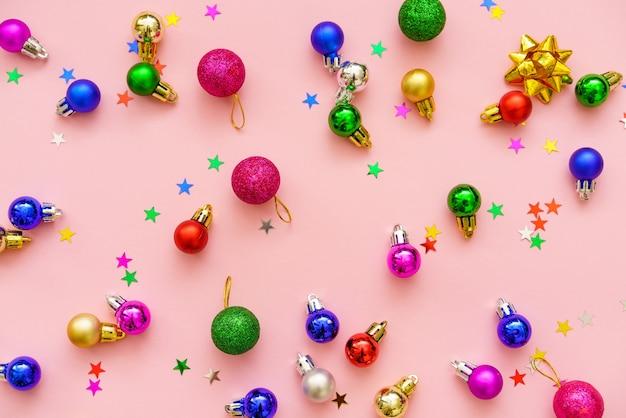 パステルピンクの背景のクリスマスの冬に新年の構成色の装飾ボールと星..。