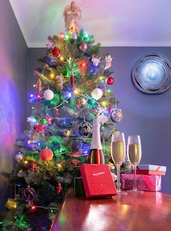 Новогоднее украшение с елкой и часами на стене в качестве фона и шампанским на переднем плане.