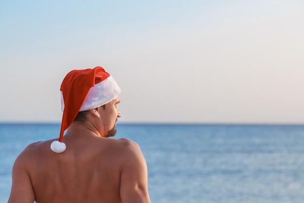 Канун нового года на пляже у моря мужчина в новогодней шапке загорает на солнышке голубое небо.