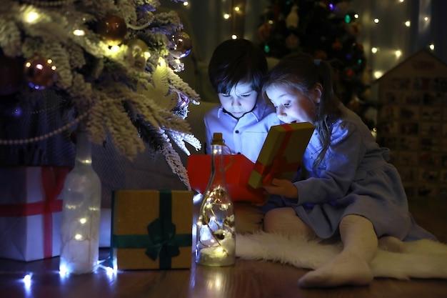 Новогодняя ночь. дом оформлен к празднику. нарядно одетая елка с гирляндой и семья с подарками и сюрпризом.