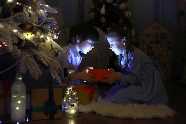 大晦日。家は休日のために装飾されています。ガーランドとギフトとサプライズのある家族がいるスマートな服装のクリスマスツリー。