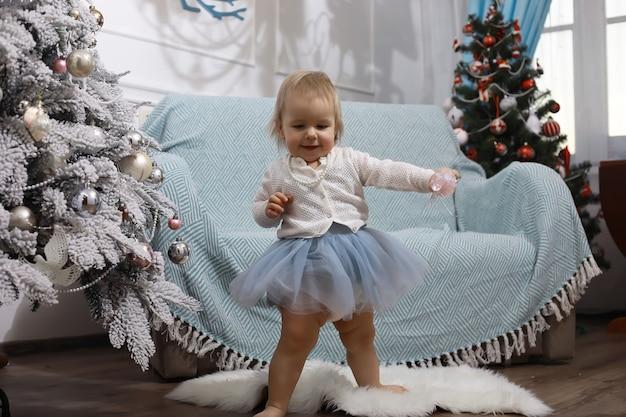 새해 전날. 집은 휴가를 위해 장식되어 있습니다. 화환이 있는 멋지게 차려입은 크리스마스 트리와 선물과 서프라이즈가 있는 가족.