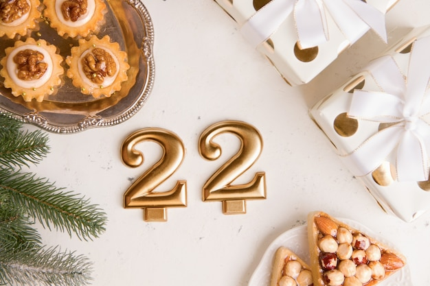 New years holiday concept. number 22 on a light background next to a sweet cookie