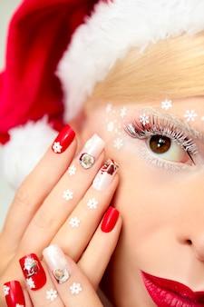 彼の目と手に雪片を使った新年のマニキュアとメイク