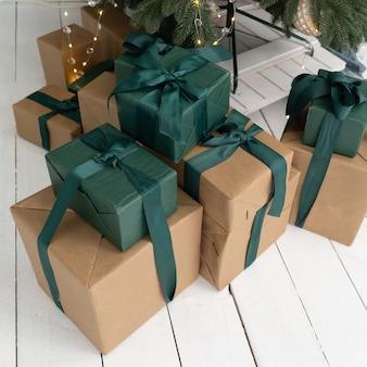 Новогодние подарки лежат под елкой. подарки в коричневых коробках и зеленой упаковке. коробки украшены лентами и бантами. крупным планом выстрел.