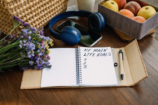 새해 결심 인생 목표 목록은 내 인생과 함께 탁자 야외 정물에 있는 열린 노트북에 있습니다.