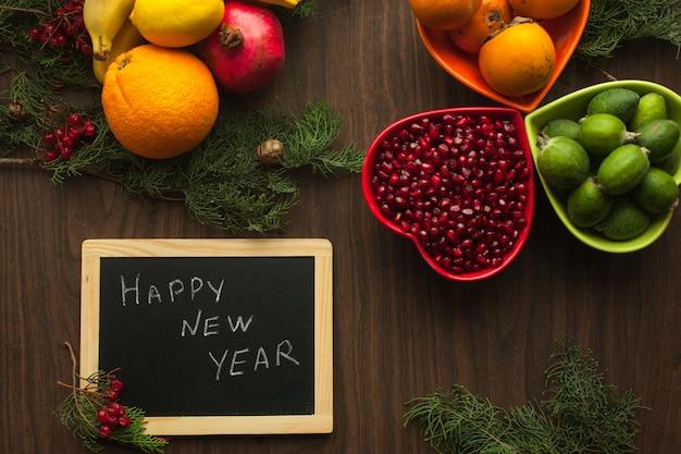 果物と黒板で飾られた新年のテーブルは、たくさんのビタミンで健康的なお祝いをします