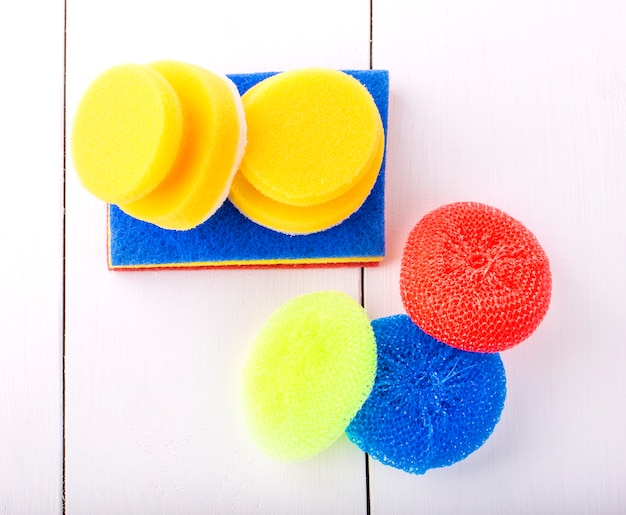 New yellow, red and blur sponge for washing dishes on a white background shot from above