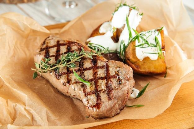 Стейк из говядины нью-йорк с печеным картофелем и сметаной