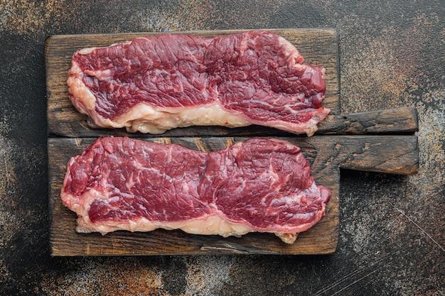 New york beef steaks, on old dark rustic background, top view flat lay