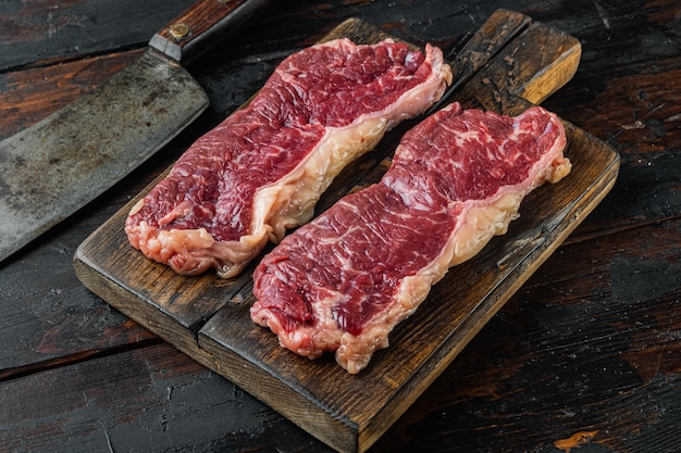 New york beef steaks, on old dark  wooden table background