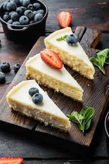 오래 된 어두운 나무 테이블에 신선한 딸기와 뉴욕 치즈 케이크 또는 클래식 치즈 케이크