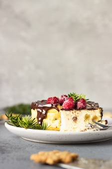 New york cheesecake with chocolate ganache, raspberries and cookies with fir branches.