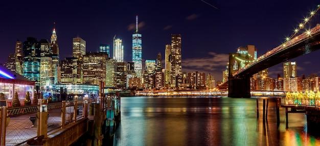 Бруклинский мост в нью-йорке и линия горизонта манхэттена с небоскребами над рекой гудзон, освещенные огнями в сумерках после захода солнца.