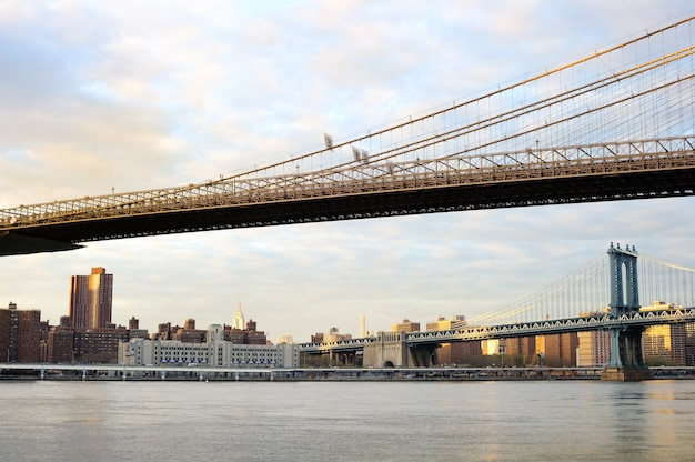 New york city brooklyn bridge with downtown skyline over east river at sunset