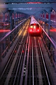 모든 조명이 켜져 있고 복사 공간이 있는 밤 맨해튼 다리의 뉴욕시 지하철