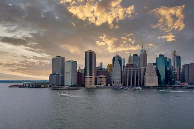 背の高い雄大な夕日が立っているマンハッタンのスカイラインに対抗するイーストリバーニューヨーク市