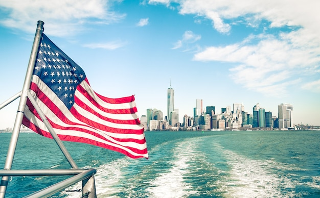 New york and manhattan skyline from hudson river with american flag