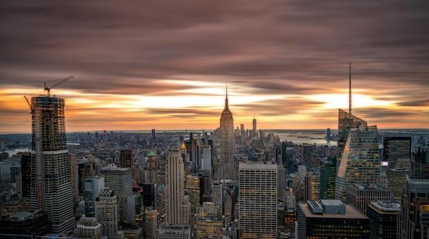 Нью-йорк на фоне линии горизонта с вершины рокфеллер-центра в сша на закате синий час