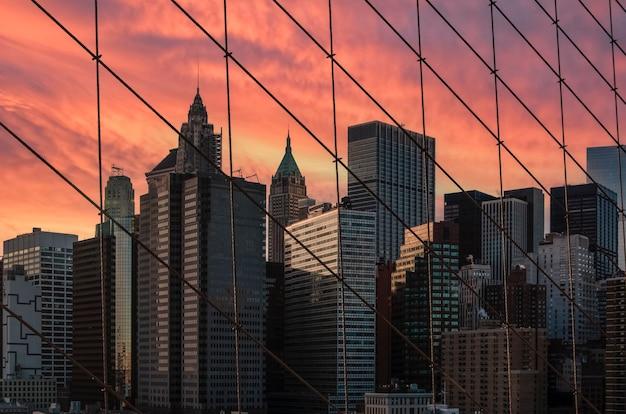 Небоскребы нью-йорка сквозь сетку бруклинского моста на фоне ярко-красного заката нью-йорк, сша