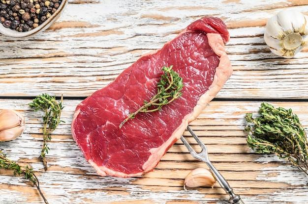 ニューヨークステーキまたはサーロインとハーブ、生の牛肉。白い木の背景。上面図。