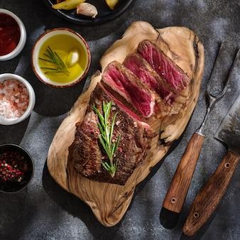 뉴욕 striploin. 회색 배경에 나무 보드에 소스와 구운 고기 스테이크를 슬라이스. 평면도.