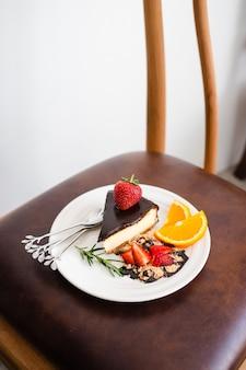 チョコレートソース、ストロベリー、オレンジでプロのスタイルをしたニューヨークスタイルのチーズケーキ。