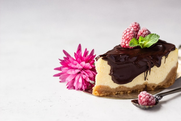 New york style cheesecake with chocolate glaze, raspberries and mint. valentine's day concept.