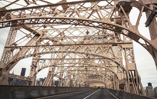 Нью-йорк, сша - 27 апреля 2016: мост эда коха квинсборо от манхэттена до квинса. автомобили на мосту квинсборо и нью-йорк манхэттен на фоне