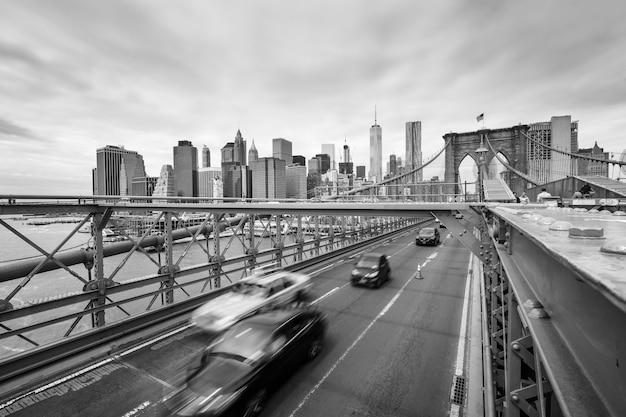 Нью-йорк, сша - 29 апреля 2016: черно-белое изображение автомобилей, пересекающих бруклинский мост в нью-йорке. манхэттен на фоне линии горизонта