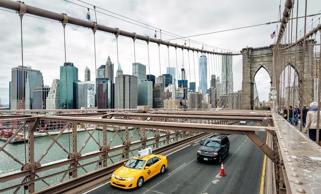 Нью-йорк, сша - 29 апреля 2016: автомобили, пересекающие бруклинский мост в нью-йорке, манхэттен на фоне линии горизонта