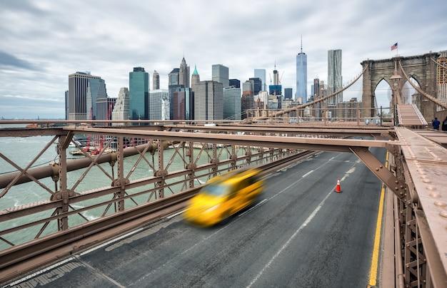 Нью-йорк, сша - 29 апреля 2016: автомобили пересекают бруклинский мост в нью-йорке в пасмурный день. манхэттен на фоне линии горизонта