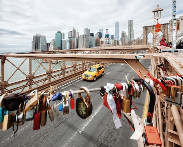 Нью-йорк, сша - 29 апреля 2016: любовь замки на бруклинском мосту. горизонт манхэттена в фоновом режиме. сосредоточьтесь на манхэттене