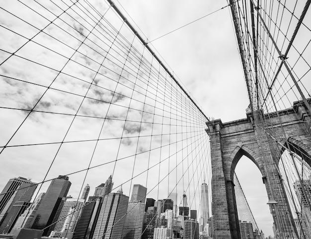 Нью-йорк, сша. черно-белое изображение бруклинского моста и манхэттена со стороны ист-ривер.