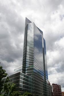 Нью-йорк, сша-июнь 16,2018: modern buliding высок в нью-йорке возле здания one world trade в сша в пасмурный день