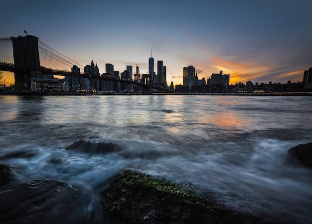 Нью-йорк, сша - 01 мая 2016: горизонт манхэттена с бруклинским мостом в вечернее время. скалы и камни на берегу ист-ривер