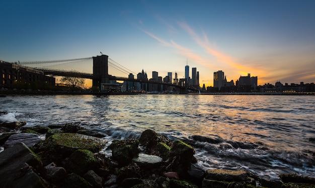 Нью-йорк, сша - 01 мая 2016: горизонт манхэттена с бруклинским мостом. скалы и камни на берегу ист-ривер