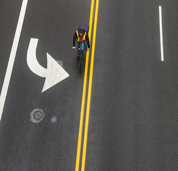 New york, usa - may 03, 2016: road markings on asphalt on the street of manhattan in new york city. motion blured cyclist moves along the road. iridescent spot of gasoline on asphalt