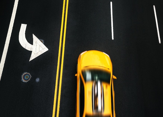 New york, usa - may 03, 2016: road markings on asphalt on street of manhattan in new york city. motion blured taxi cab moves along the road with a high speed. iridescent spot of gasoline on asphalt