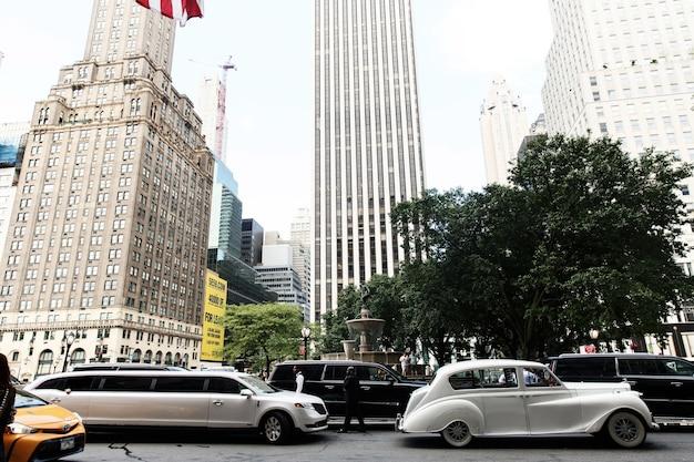 New yorkの通り沿いに白いレトロ車と新しいリムジンが乗る