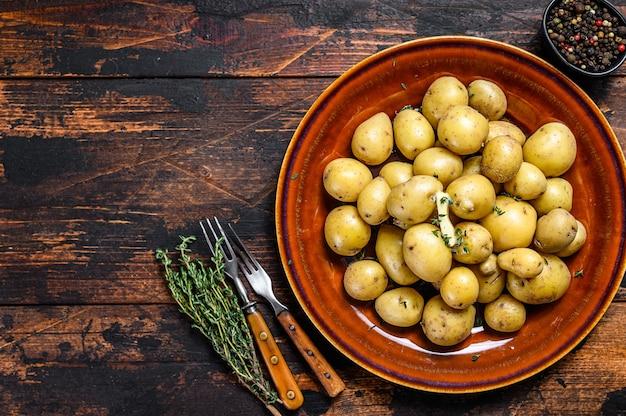バターと刻んだディルを添えた新しい若い茹でたジャガイモ。暗い木の背景。上面図。スペースをコピーします。