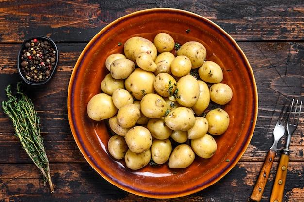 バターと刻んだディルを添えた新しい若い茹でたジャガイモ。暗い木の背景。上面図。